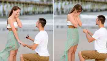 Putting on the engagement ring in front of the pier