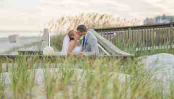 Portrait of bride and groom kissing behind the sea grass at the Ocean Club in Myrtle Beach