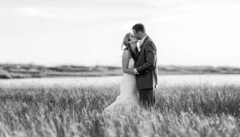 Black and white of couple kissing with sunlight reflecting on the beach grass - Holden Beach
