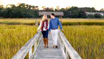 Couple walking down marsh boardwalk together at sunset
