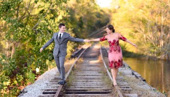 Couple holding hands walking down the train track rails - Conway River Walk
