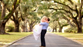 Man lifting fiance into the air under Live Oaks - Litchfield Plantation