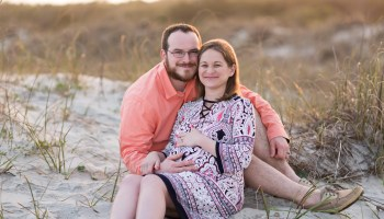 Maternity portraits of man and woman sitting by the dunes - Huntington Beach State Park