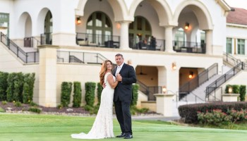 Bride and groom with clubhouse in the background - Members Club at Grande Dunes