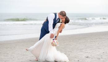 Groom dipping back bride in front of the ocean - Avista Resort - North Myrtle Beach