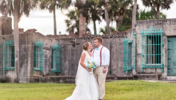 Bride looking into the eyes of the groom behind the castle - Atalaya Castle - Huntington Beach State Park