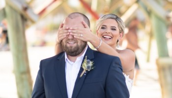 First look with bride putting her hands around the groom's eyes - Folly Beach - Charleston