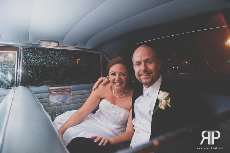 Wedding couple inside of getaway vehicle