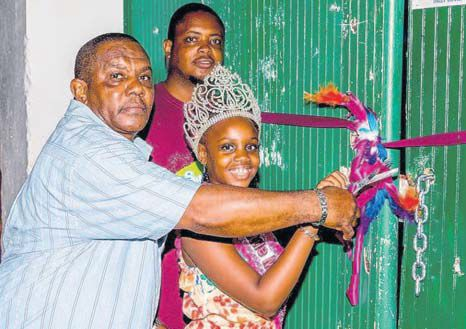 Commissioner of Culture Rolando Wilson (left) is assisted by Saba Festival Foundation President Vito Charles and Little Miss Saba Meliegqia Hughes in officially opening the gates to the Carnival Village. (STK photo)