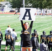 """Nicole Brey holds up an """"A"""" sign to the crowd at an Ottawa Braves college football game."""