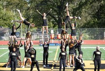 Nicole Brey (middle top) and her Ottawa Braves cheer team perform their stunt routine during a college football game.