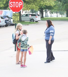Sabetha Elementary School Principal Rusty Willis speaks to Kenzie and Klaira Dempewolf on the first day of school on Thursday, August 19.