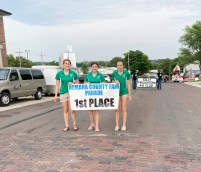Nemaha County 4-H Ambassadors walk in the Nemaha County Fair parade with the first place float, which was the Kelly Twilighters. Pictured are (L-R) Leah Renyer, Kendall Durland and Monica Stallbaumer