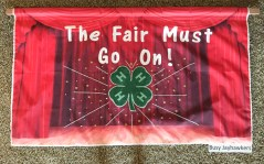 The Busy Jayhawkers 4-H Club receives a blue ribbon on their club banner promoting the 2021 fair theme.