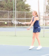 Junior Kate Beyer hits the ball back to her opponent during the tennis meet on Monday, September 20.