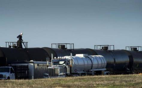 A tanker truck is filled from railway cars containing crude oil at McClellan Park in March.