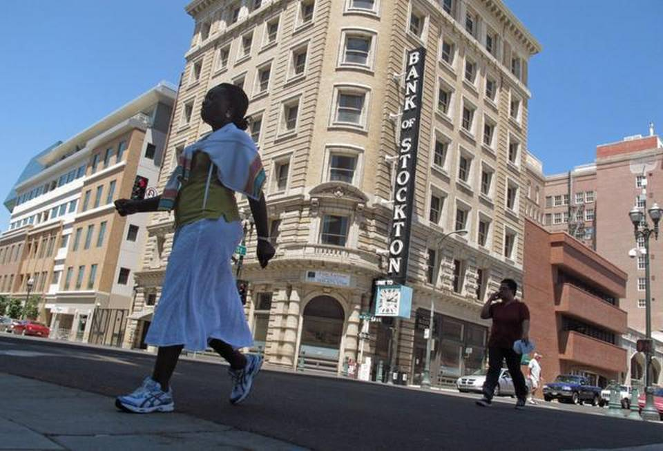 Pedestrians cross a street near the Bank of Stockton in Stockton, Calif.