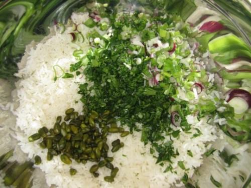 In den abgekühlten Reis zuerst das Grünzeug und die Pistazien geben.