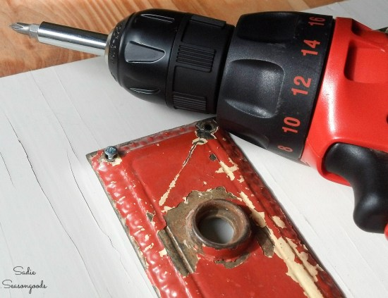 Attaching a door escutcheon or doorknob keyplate to a cupboard door for foyer wall decor