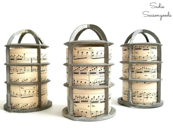 Rustic Christmas decor with the Christmas luminaries that are made with light bulb cages and old sheet music