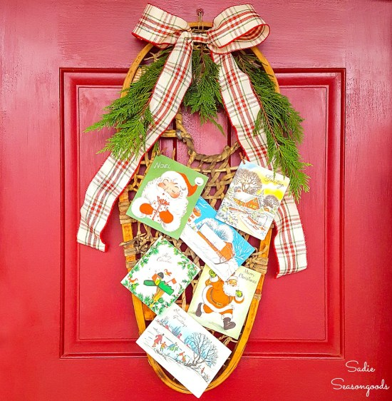 Rustic Christmas decor and front door decor by using a wooden snowshoe or vintage snow shoe as a holiday wreath