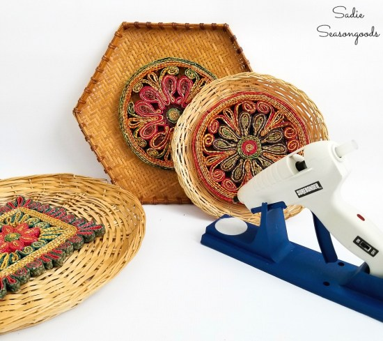 Using hot glue to attach the woven trivets to hanging baskets for a Boho wall hanging or gallery wall