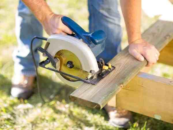 Mann schneidet ein Holzbrett mit einer Kreissäge