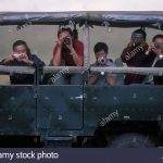 Africa, Kenya, Masai Mara Game Reserve, Asian tourists pointing cameras from safari truck on game drive
