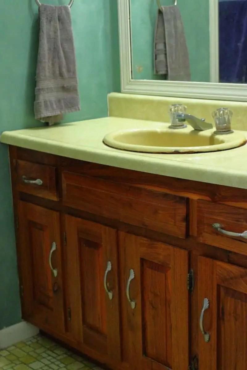 Yellow countertop, green wall and wood bathroom cabinet