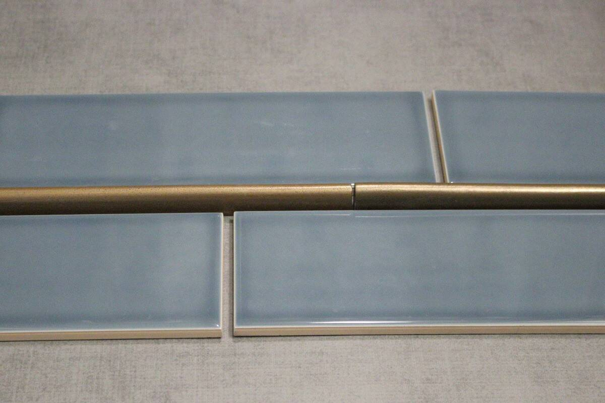 Bathroom remodel material choices - blue subway tiles with bronze accent strip