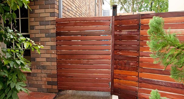 Brick wall with modern style garden gate and fence using horizontal slats
