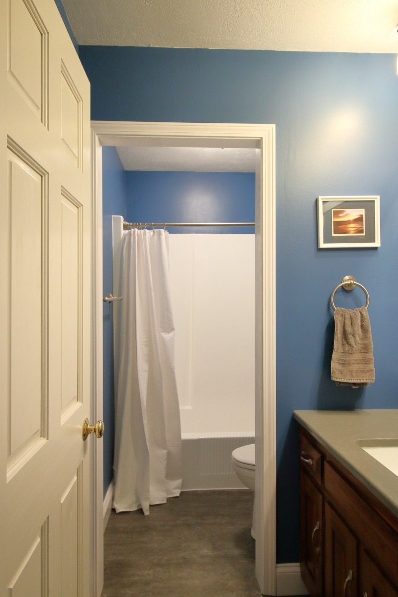 Bathroom remodeling project - after. Dark blue walls, dark grey counter and floor, white tub, sink and toilet.