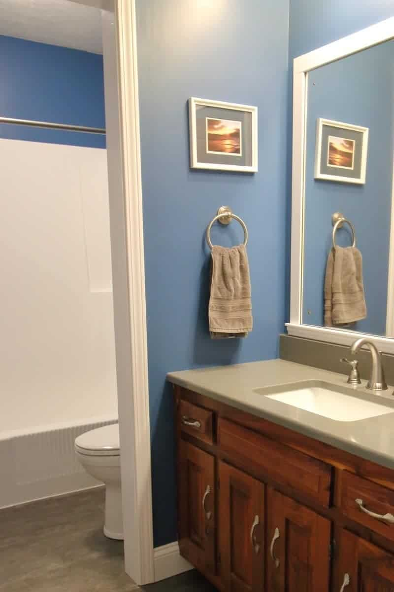 Bathroom remodel costs for a dark grey and blue bathroom with white trim.