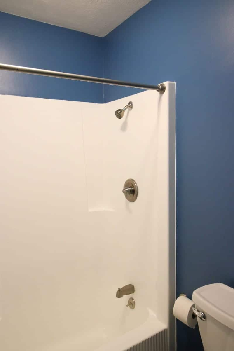 White tub and dark blue walls in after picture of bathroom remodel