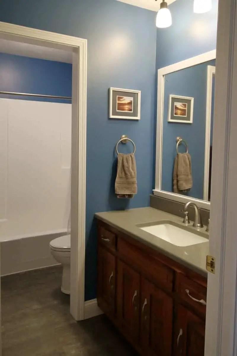 Photo of dark blue bathroom with white wood DIY bathroom mirror frame project