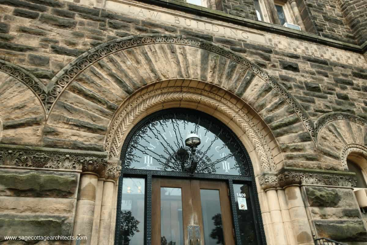 Rough cut stone arched entry to Richardsonian Romanesque university building.