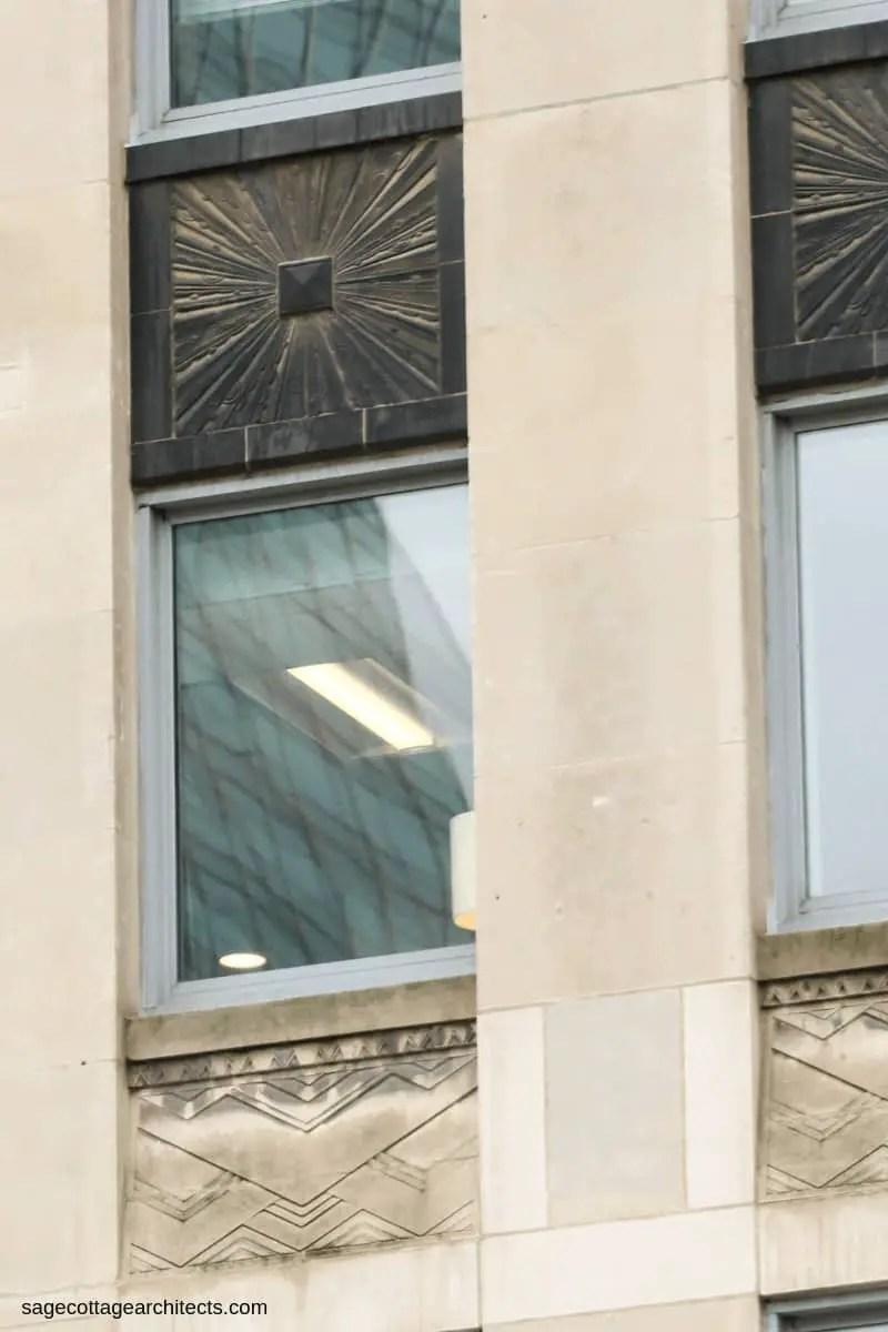 Black Art Deco sunburst spandrel panel above a window with carved chevron limestone panel underneath