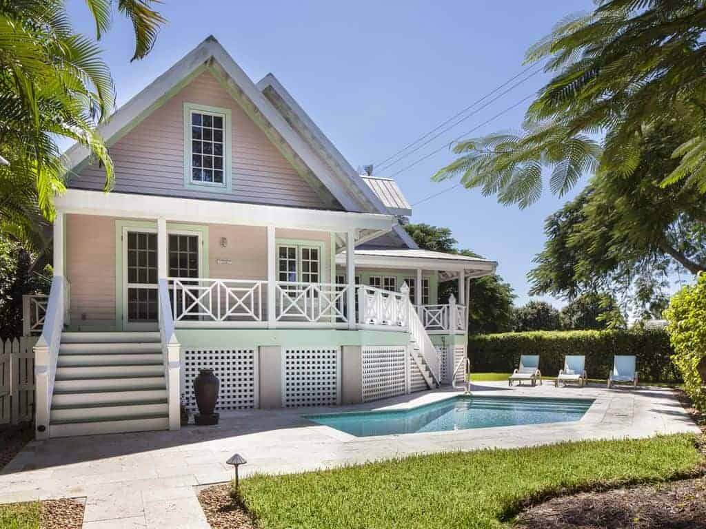 Photo of a Key West style beach vacation home with pink siding and white trim.