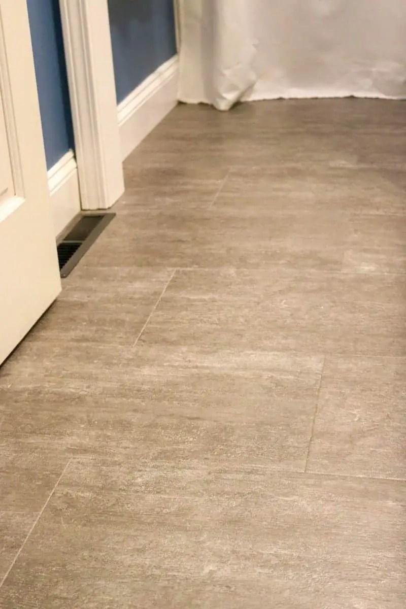 Photo of grey luxury vinyl tile flooring, dark blue walls and white trim.
