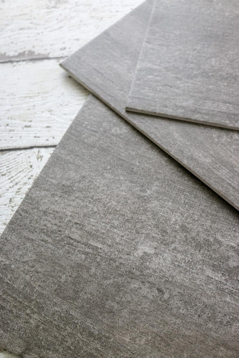 Photo closeup of dark grey luxury vinyl tile flooring pieces