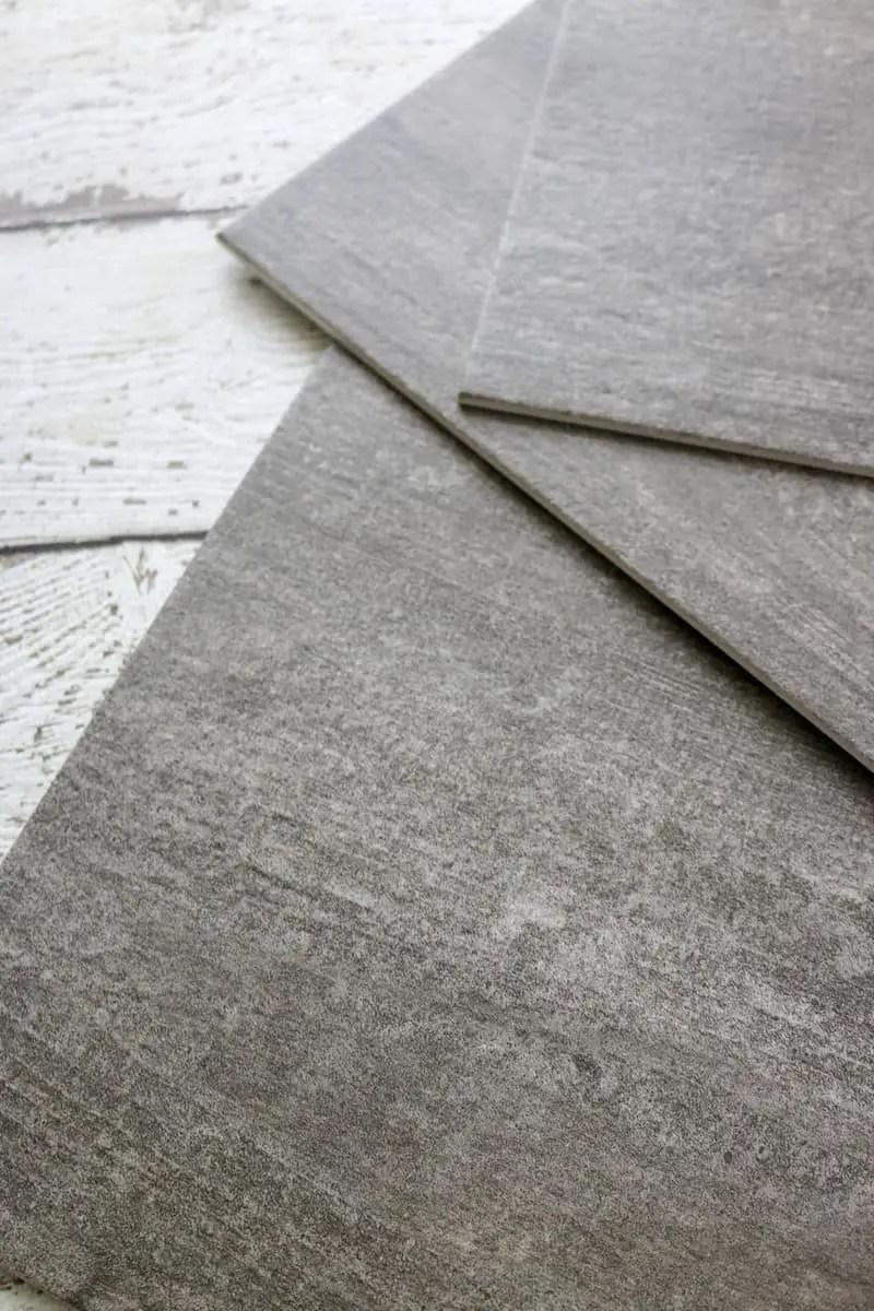 Photo closeup of dark grey luxury vinyl tile flooring pieces