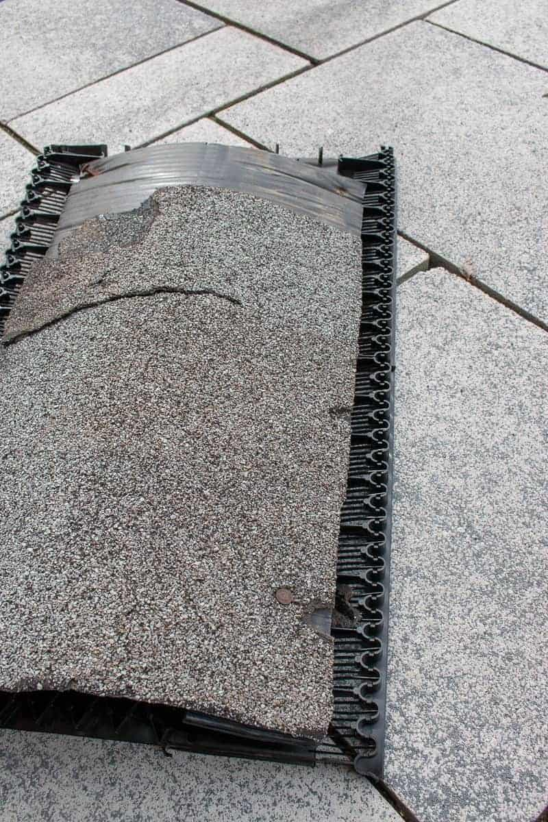 Photo of asphalt shingle with roof ridge vent underneath.