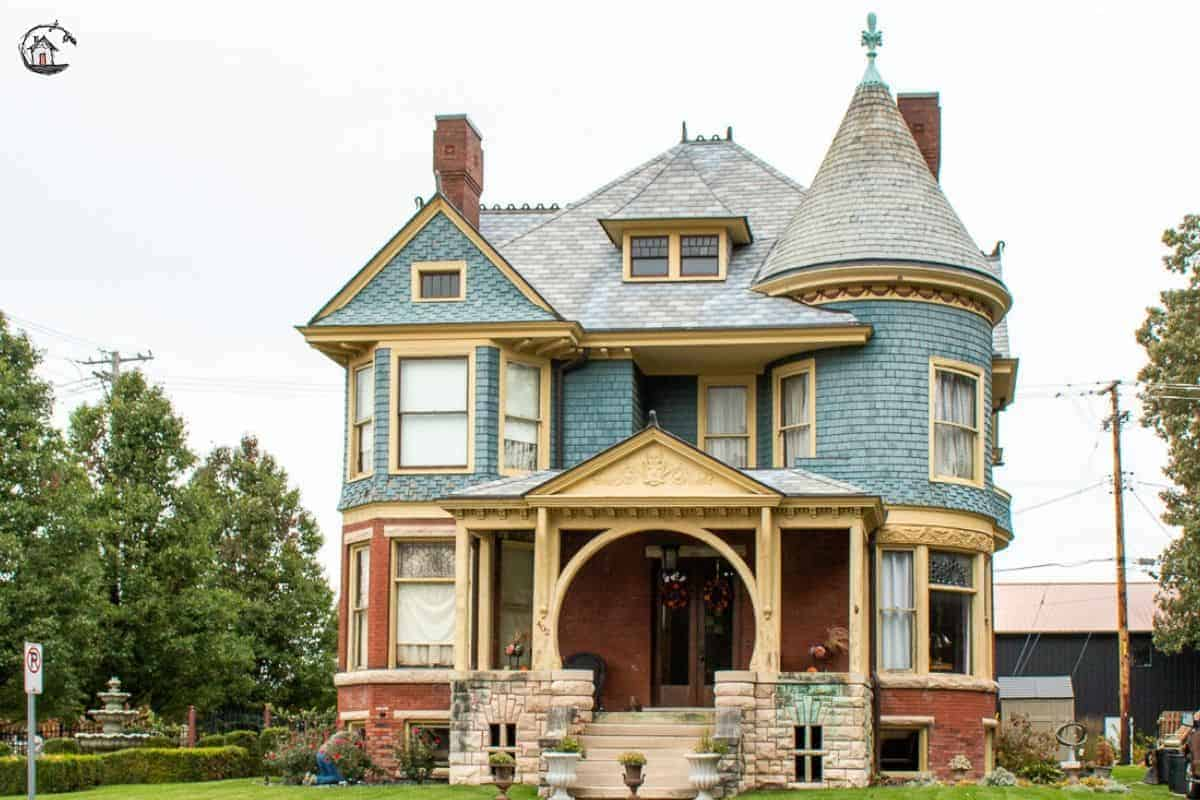 Photo of Victorian home with large front porch, turret, and witch's hat roof.
