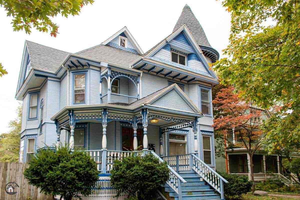 Photo of Victorian home with blue exterior, painted gingerbread and large front porch in a neighborhood filled with old houses.