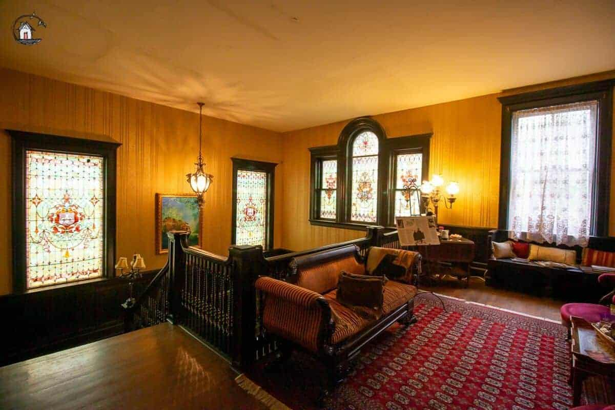 Photo of the second floor sitting area, with large stained glass windows, in the Vrooman Mansion.