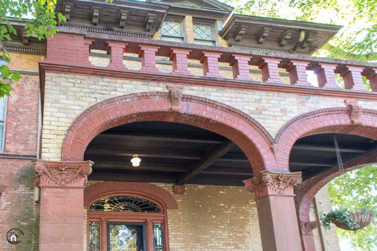 Photo of the entry porch to the Vrooman Mansion with red brick arches.