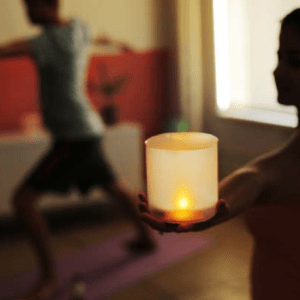 yoga pose with solar candles in hand