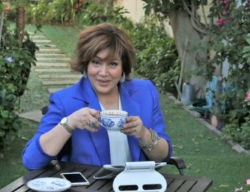 Sahar wearing blue blazer sitting in garden and holding her coffee cup