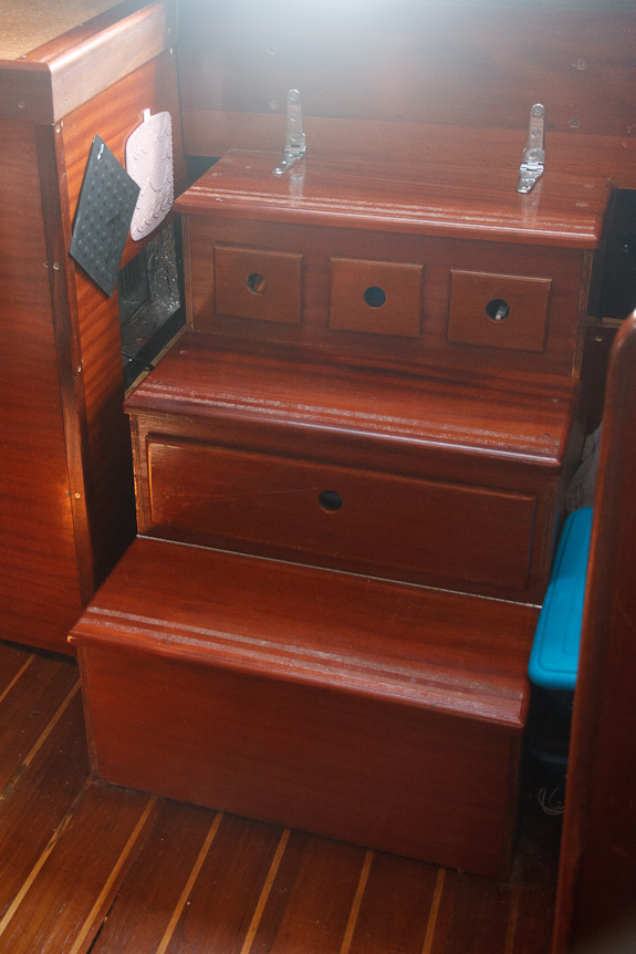 Stairs with built in boat storage drawers replace a typical companion way ladder