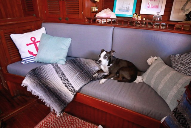 Pillows and rugs add color to a dark wood interior of the Vagabond 42 sailboat.